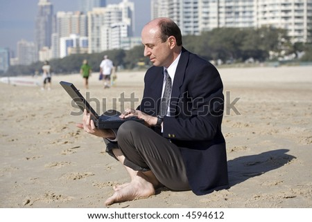 Image of a business man sitting on the beach using his computer. - stock photo