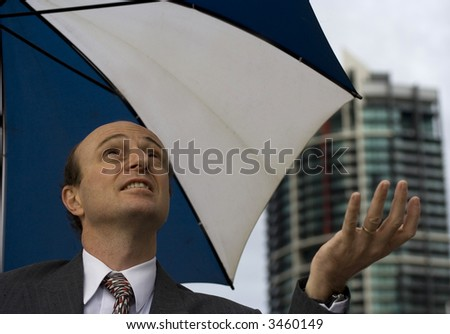 Image of a business man taking a business rain check. - stock photo