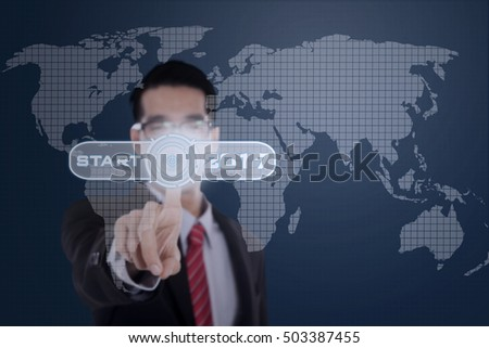 Image of a businessman pressing a virtual start button with numbers 2017 and world map on the futuristic screen
