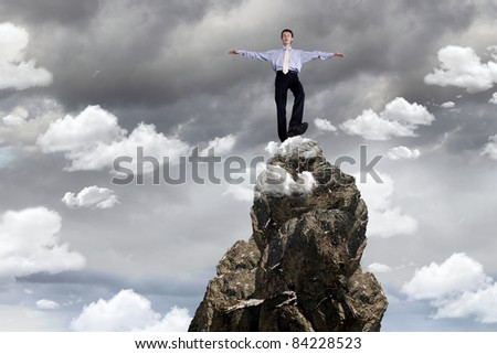 Image of a businessman standing on the top of a high mountain - stock photo