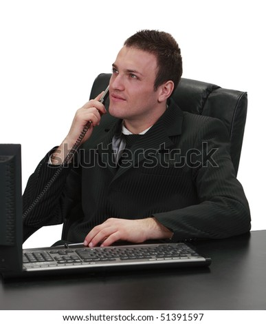 Image of a businessman using a telephone while sitting to his work desk, isolated against a white background. - stock photo