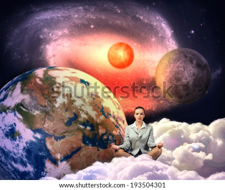 image of a businesswoman meditating in the clouds in space. Elements of this image furnished by NASA - stock photo