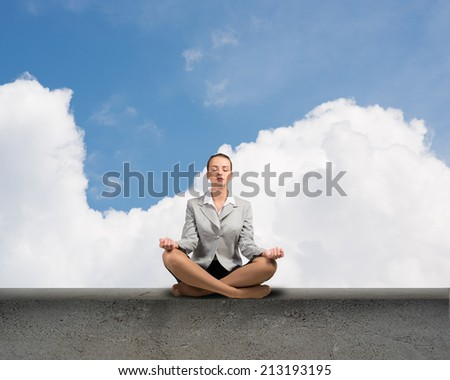 image of a businesswoman meditating on a concrete parapet - stock photo