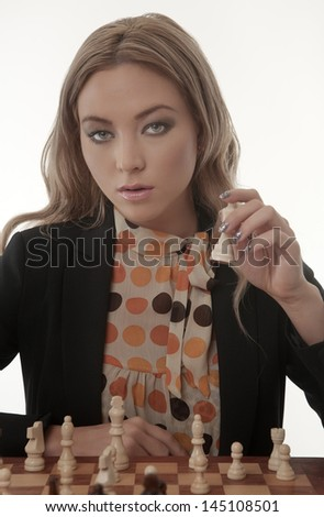 Image of a businesswoman playing chess shot in the studio - stock photo