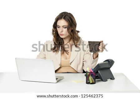 Image of a busy businesswoman while looking at her laptop and holding a coffee - stock photo
