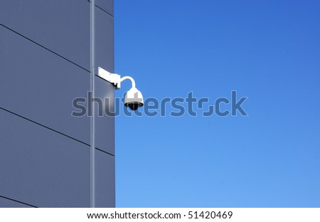 Image of a CCTV dome camera attached to the side of a large modern building