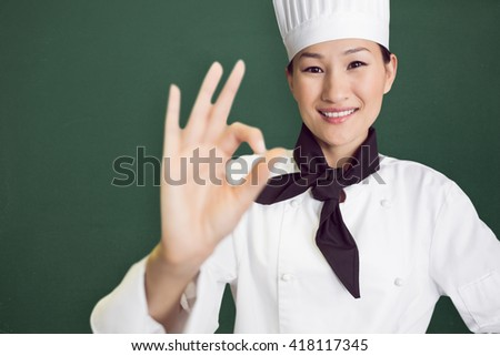 Image of a chalkboard against smiling female cook gesturing okay sign in kitchen - stock photo
