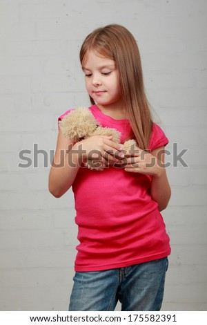 Image of a charming little girl with toy on a gray background
