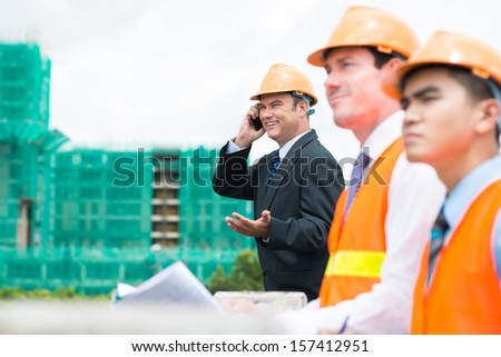 Image of a cheerful engineer calling by the phone on the foreground - stock photo