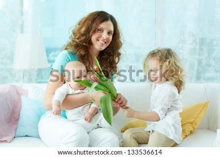 Image of a cheerful mom and kids holding a bouquet of fresh spring tulips