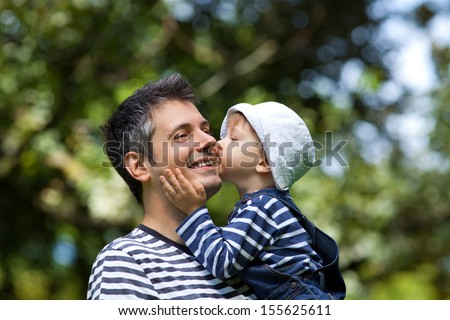 Image of a child kissing a father on a cheek, shallow depth of field - stock photo