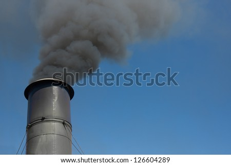 image of a chimney or smoke stack with thick black smoke coming out of it against a blue cloudless sky - stock photo