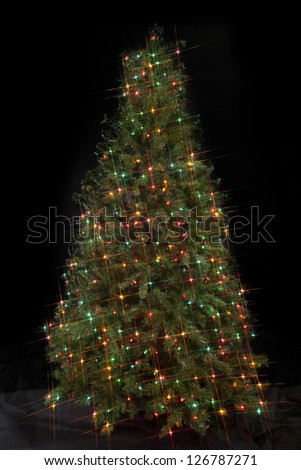 Image of a Christmas tree decorated with decorative Christmas electric lights against dark background. - stock photo