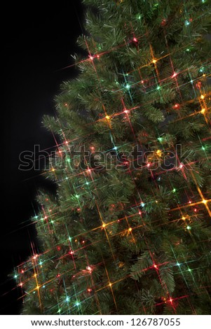 Image of a Christmas tree decorated with decorative Christmas lights against a dark black background. - stock photo