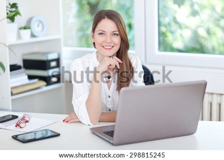 Image of a confident young woman sitting at working desk - stock photo