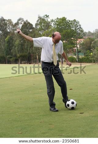 Image of a confused business man attempting to hole out with a soccer ball. - stock photo