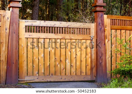 Image of a contemporary, decorative wooden gate as an entrance to a formal garden.