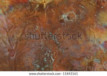 Image of a copper sheet with spots of patina as well as multi colored heat stress spots - stock photo