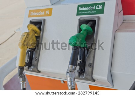 Image of a couple of petrol fuel pump nozzles on the pump at petrol station. One is unleaded E10 and has a green nozzle while the other is Unleaded 91 and has a yellow and dirty nozzle. - stock photo