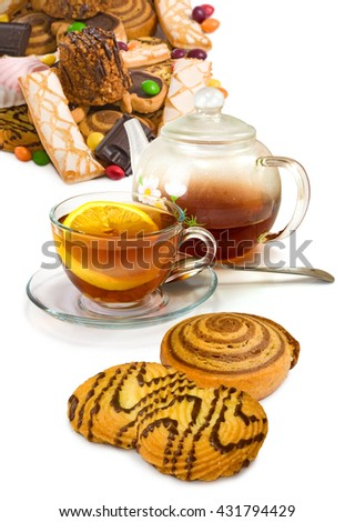 image of a cup, teapot with tea and sweets closeup