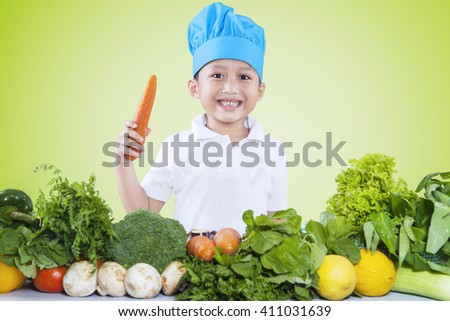 Image of a cute boy preparing fresh vegetables while holding a carrot and wearing a cooking hat - stock photo