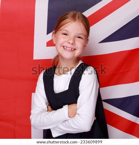 Image of a cute cheerful little schoolgirl with a sweet smile in school uniform on background of the flag the UK/British young schoolgirl smiling on the background of the flag of England - stock photo