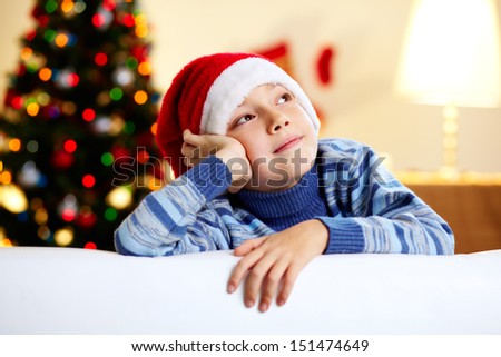 Image of a cute guy in a Santa hat dreaming of a new year�¢??s celebration - stock photo