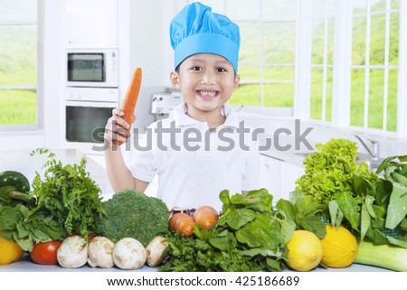Image of a cute little boy wearing a cooking hat while preparing vegetables and holding a carrot in the kitchen - stock photo