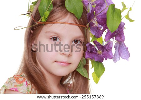 Image of a cute little girl in a summer dress with a beautiful hairdo with fresh purple clematis isolated on white - stock photo