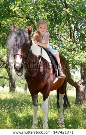 Image of a cute smiling little girl with long blonde hair smiling and riding a pony outdoors