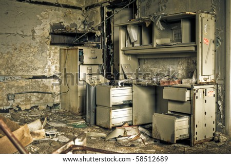 Image of a destroyed office in a derelict abandoned police station surrounded by crumbling walls with peeling paint. - stock photo