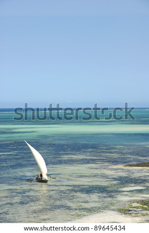 Image of a dhow on turquoise lagoon