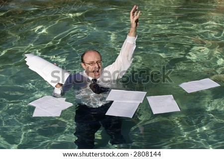 Image of a drowning business man with paperwork floating around him. - stock photo