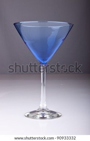 Image of a fancy blue martini glass on gray.