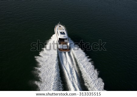 Image of a fast speedboat sailing in a dark sea on a sunny afternoon
