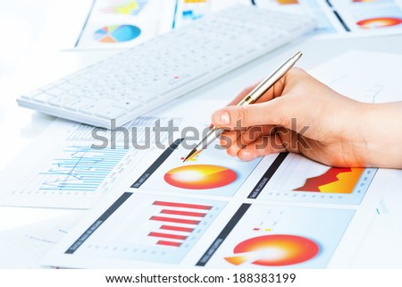 image of a female hand pointing to the financial growth charts - stock photo