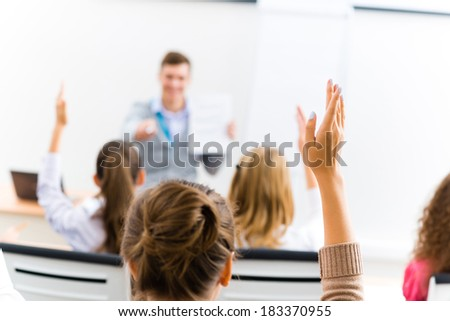 image of a female hand raised in university classroom - stock photo