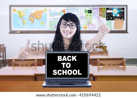 Image of a female high school student showing thumbs up with a text of back to school on the laptop screen - stock photo