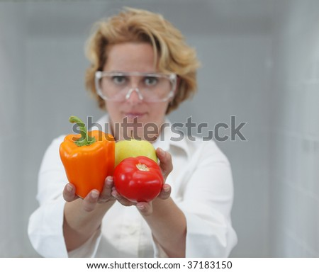 Image of a female researcher offering a tomato and an apple to suggest the idea that healthy eating is recommended also by scientists.Specific lighting for a classical research laboratory. - stock photo