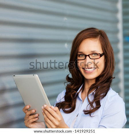 Image of a female working on the tab and smiling for the camera.