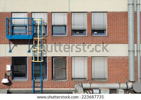 Image of a fire escape ladder leading onto a roof outside an office block - stock photo