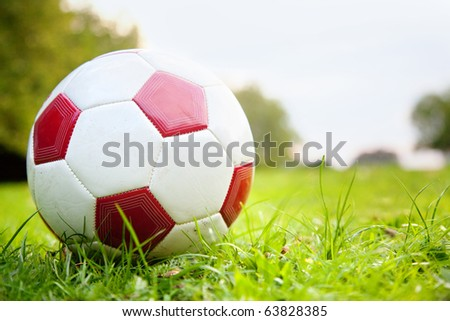 Image of a football lying over green grass outdoors - stock photo