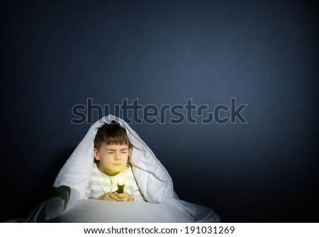 image of a frightened boy under the covers with a flashlight - stock photo