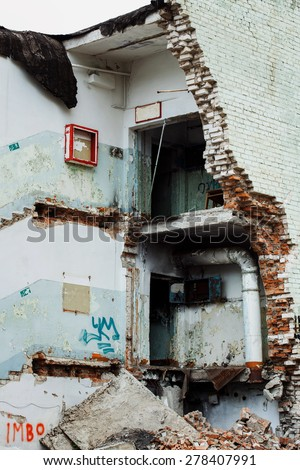 Image of a front of a ruined building with collapsed brick walls and floor. Concept of natural disaster, war. - stock photo