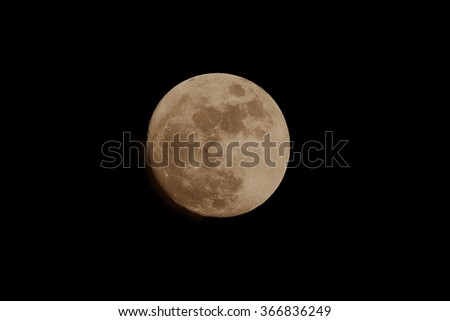 Image of a full amber moon shot during the evening shows orange color the planet casts at certain times of the year.   - stock photo