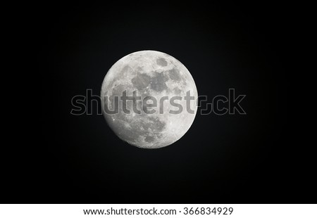 Image of a full moon shot during the evening shows the moonlight highlighting features of the planet.  - stock photo