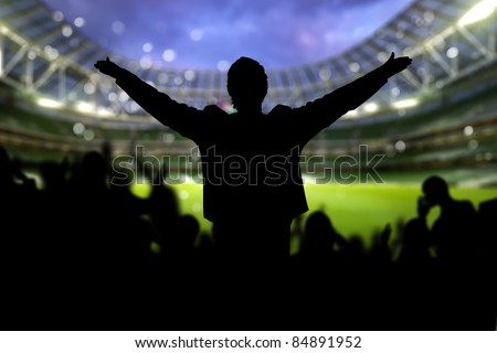 Image of a full stadium with silhouettes of fan on the foreground - stock photo