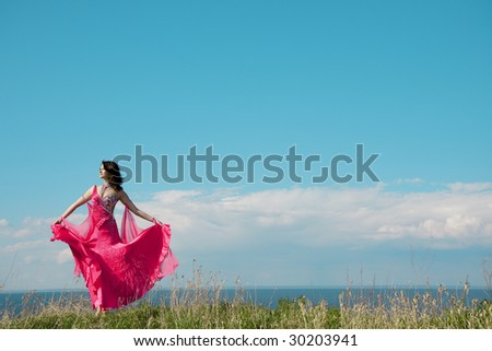 Image of a girl in bright pink dress against the backdrop of blue sky. - stock photo
