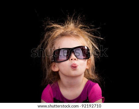 Image of a girl sticking her tongue out with sunglasses on. - stock photo