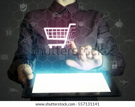 Image of a girl with a tablet in hands. She touches shopping cart icon.  Online shop concept.